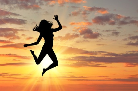 freedom concept: Concept of happiness and freedom. Silhouette of happy woman jumping at sunset Stock Photo