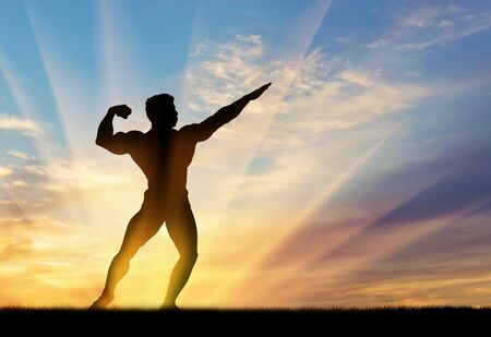 pres: Concept of beauty and sports. Silhouette of bodybuilder poses at sunset