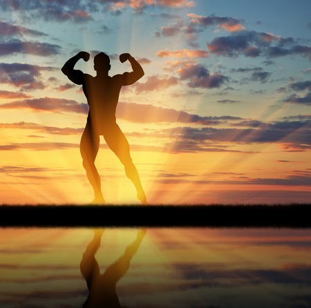 pres: Concept of beauty and sports. Silhouette of bodybuilder posing at sunset and its reflection in water Stock Photo