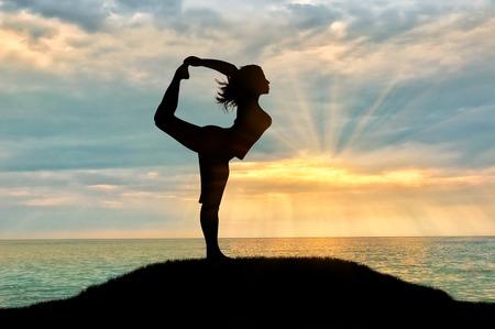 Concept van meditatie en ontspanning. Silhouet van een meisje het beoefenen van yoga les op een achtergrond van zee zonsondergang Stockfoto