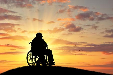 Concepto de discapacidad y la vejez. Silueta de la persona con discapacidad en una silla de ruedas en el fondo de la puesta del sol Foto de archivo