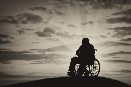 Concept of disability and old age. Silhouette of disabled person in a wheelchair on the sunset background
