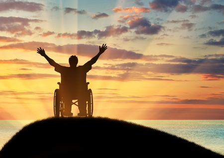 Concept of disability and disease. Silhouette happy disabled person in a wheelchair and sea sunset