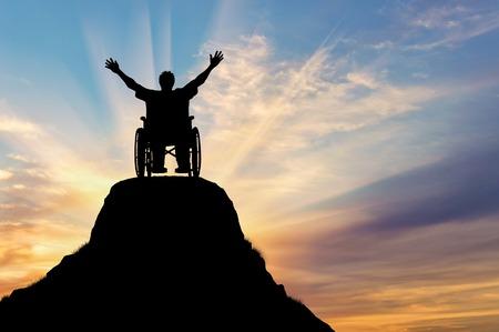障害や病気の概念。幸せなシルエットが山で車椅子の方を無効に