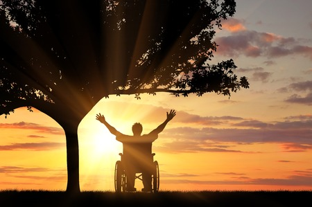 crippled: Concept of disability and disease. Silhouette happy invalid under the branches of a tree at sunset Stock Photo