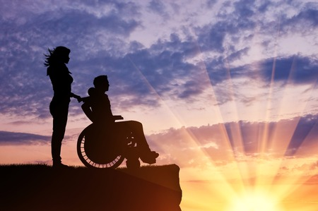 crippled: Concept of disability and disease. Silhouette of disabled person with a guardian on the hill in the evening