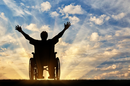 Concept of disability and disease. Silhouette happy disabled person in a wheelchair at sunset