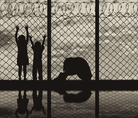 illegals: Concept of refugee. Silhouette of a refugee family, a mother in despair with children on the background of the border and reflection