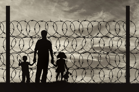 middle east crisis: Silhouette of a family with children of refugees and fence with barbed wire on the background of the beautiful sky Stock Photo
