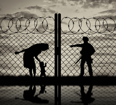 illegals: Concept of the refugees. Silhouette refugee mother with a baby and a border guard at sunset and reflection