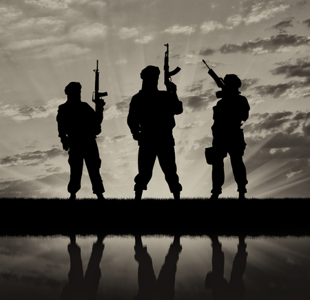 terrorists: Concept of a terrorist. Silhouette of terrorists with a rifle and a reflection on the water at sunset and reflection