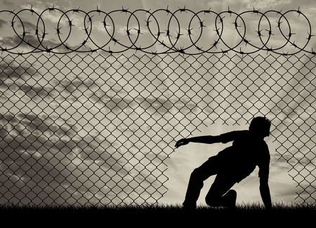 Concept of the refugees. Silhouette of refugees crossed the border illegally through the hole in the fence Imagens