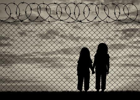 Concept van de vluchtelingen. Silhouet van hongerige kinderen in wanhopige vluchtelingen in de buurt van het hek bij zonsondergang Stockfoto