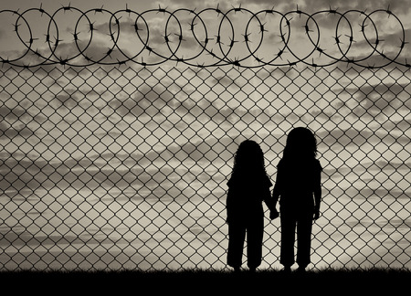 Concept of the refugees. Silhouette of hungry children in desperate refugees near the fence at sunset Archivio Fotografico