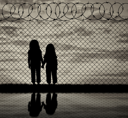 middle east war: Concept of the refugees. Silhouette of hungry children in desperate refugees near the fence at sunset and reflection