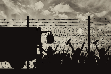 middle east crisis: Concept of the refugees. Silhouette of humanitarian assistance to refugees near the fence with barbed wire