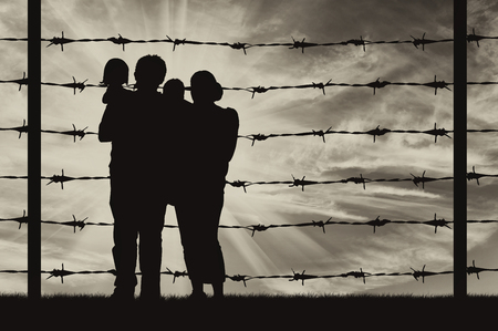 illegals: Concept of refugee. Silhouette of a family with children of refugees and fence with barbed wire