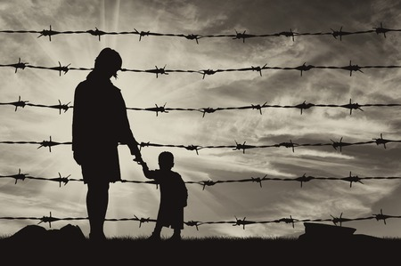 illegals: Concept of refugee. Silhouette of hungry refugees mother and child near the fence of barbed wire Stock Photo