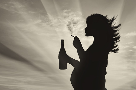 malos habitos: Concepto del embarazo y los malos hábitos. Silueta de una mujer embarazada fuma un cigarrillo con una bebida alcohólica al atardecer Foto de archivo