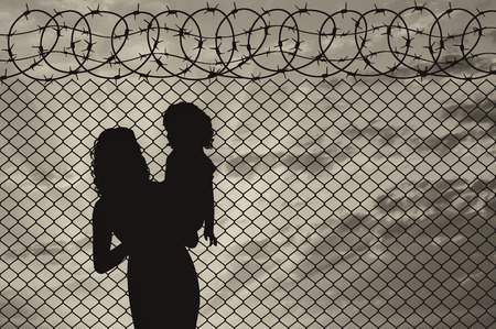 illegals: Concept of refugee. Silhouette of mother and child refugees at the border fence at sunset Stock Photo