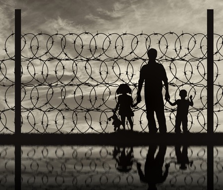 illegals: Silhouette of a family with children of refugees and fence with barbed wire on the background of the beautiful sky and reflection