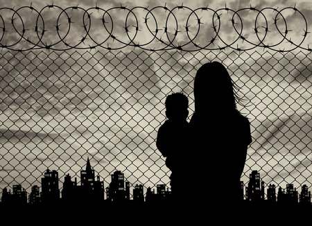 middle east war: Concept of the refugees. Silhouette refugee mother with a baby in the background of the fence and the city at sunset Stock Photo