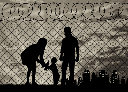 illegals: Concept of the family of refugees. Silhouette of refugee families near the fence on the border on the background of the city in the distance at sunset