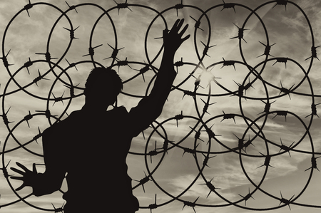middle east crisis: Concept of security. Silhouette of refugee men and metal fence with barbed wire on the background of the beautiful sky Stock Photo