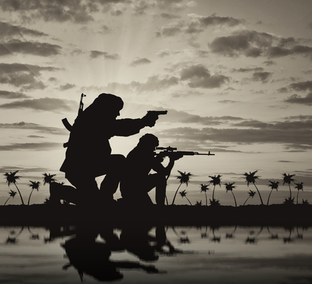 terrorists: Concept of terrorism. Silhouette of a terrorists with a rifle on a background of sunset and palm trees and reflection Stock Photo