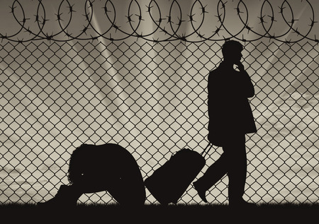 illegals: Concept of the refugees. Silhouette of a couple of refugees near the border fence at sunset Stock Photo