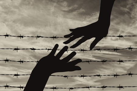 poverty relief: Concept of refugee. Silhouette helping hand to refugees on the background of the fence of barbed wire Stock Photo