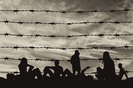 illegals: Concept of refugee. Silhouette of a crowd of refugees rest on the ground near the fence or barbed wire