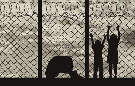 illegals: Concept of refugee. Silhouette of a refugee family, a mother in despair with children on the background of the border