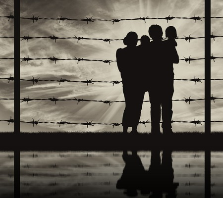 middle east crisis: Concept of refugee. Silhouette of a family with children of refugees and fence with barbed wire and reflection
