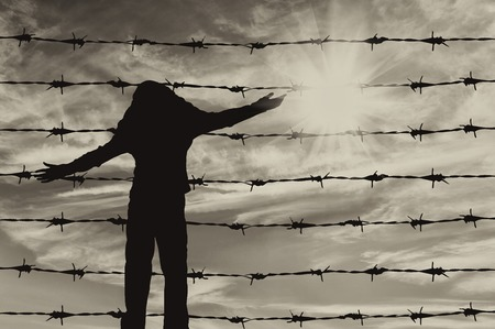 middle east war: Concept of refugee. Silhouette of a refugee child near the fence of barbed wire Stock Photo