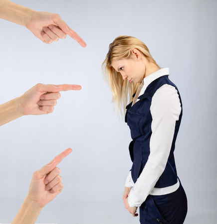 reprimand: Concept of blame and shame. Sad girl in a suit and hands pointing at it Stock Photo