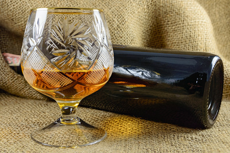 crystal glass: Aged whiskey in a crystal glass next to the bottle. design element