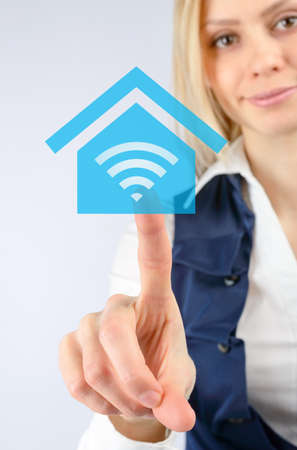 wi fi: Wireless Internet concept. Business woman clicks on the icon Wi fi in the house