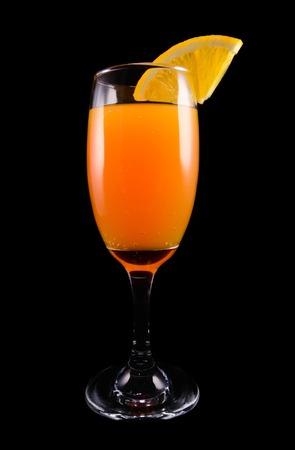 黒の背景のクローズ アップにオレンジのスライスとカクテルのミモザ