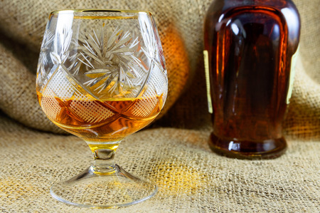 crystal glass: Aged whiskey in a crystal glass beside the bottle. design element