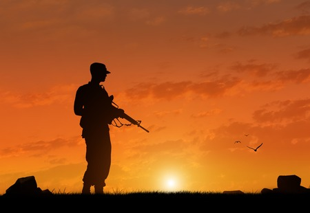Silhouette of a terrorist with a weapon at sunset. The concept of terrorism and war Reklamní fotografie