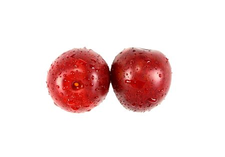 Two ripe juicy plum isolated on a white background Фото со стока