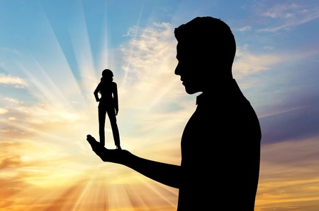 feminism: Feminism concept. Silhouette of a man holding a small woman.