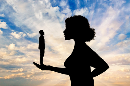 dominance: Silhouette feminist holding a small man. Concept of feminism.