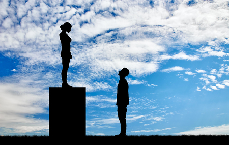 dominance: Feminists silhouettes standing on a pedestal looking down at the man. Feminism concept Stock Photo