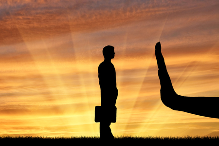 objections: Discrimination and racism concept. Silhouettes of hands stops a man on the sunset background
