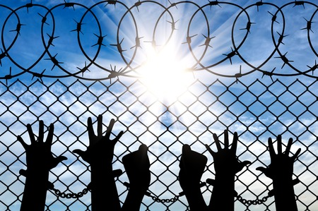 handcuffed: Silhouette of a crowd of hands in handcuffs near the fence with barbed wire