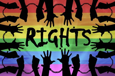 accused: Gay rights concept. Silhouette gay hands in handcuffs on the background of the rainbow
