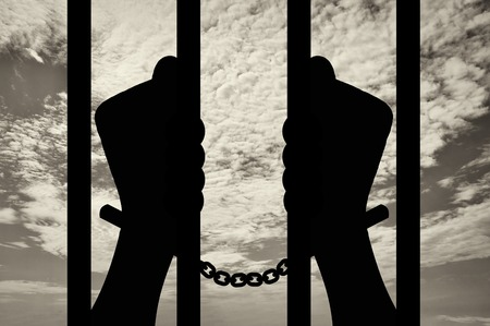 Freedom concept. Silhouette of human hands in handcuffs behind bars