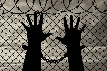 Freedom concept. Silhouette of human hands in handcuffs near the fence with barbed wire